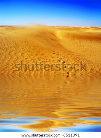 Lost in the Desert Mirage with footprints leading from water up into the Dunes  with sand blowing of the top. - stock photo