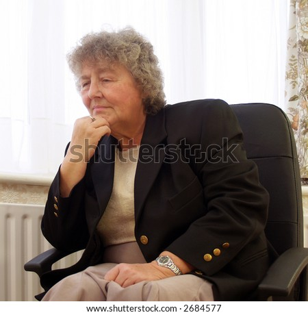 Lost in thought senior female in office - stock photo