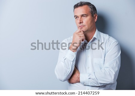 Lost in thoughts. Portrait of thoughtful mature man in shirt holding hand on chin and looking away while standing against grey background - stock photo