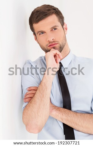 Lost in thoughts. Thoughtful young man in shirt and tie looking away and holding hand on chin while leaning at the wall - stock photo