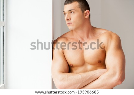 Lost in thoughts. Thoughtful young muscular man looking away while standing near the window - stock photo