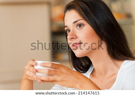 Lost in thoughts. Thoughtful young woman holding coffee cup and looking away while sitting in coffee shop - stock photo