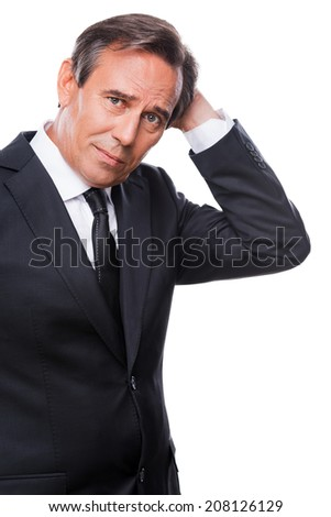 Lost in thoughts. Worried mature man in formalwear holding hand in hair and looking at camera while standing isolated on white background - stock photo