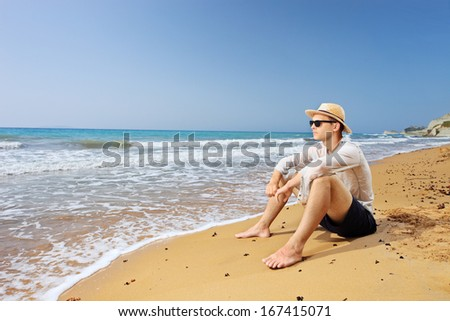 Lost male tourist sitting on a beach and thinking, Corfu island, Greece