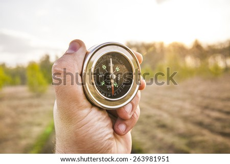 lost man holding compass in middle of forest with many paths to choose from Which direction to go? North or south? Decisions to be made Background of summer or spring meadow or field  - stock photo