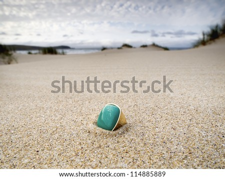 lost ring on the beach and half buried in the sand