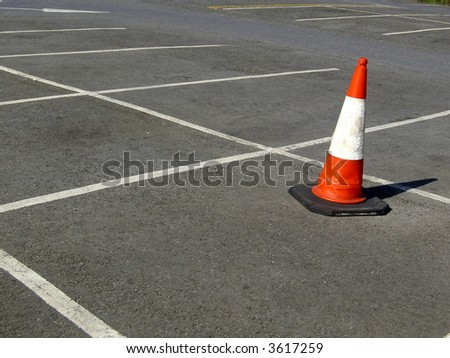 lost traffic cone in the middle of a carpark - stock photo