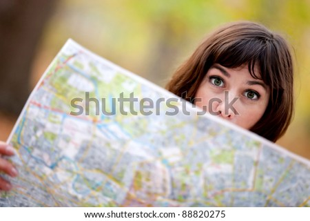 Lost woman in the countryside holding a map - stock photo
