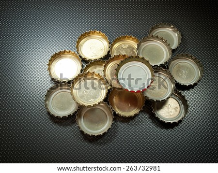 Lot of bottle caps on a gray background with pattern.