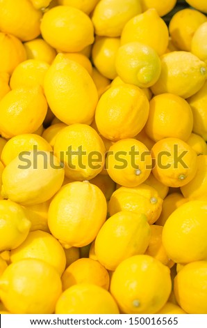 Lot of bright yellow lemons in supermarket - stock photo