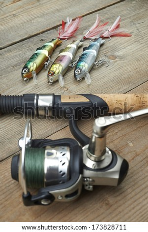 lot of colorful lures with the fishing rod on the wooden pier - stock photo