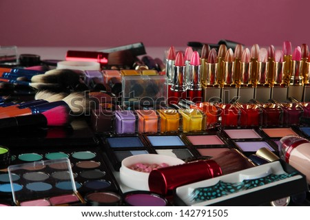 Lot of different cosmetics on purple background - stock photo