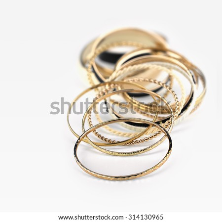 Lot of golden bracelets  in a white background - stock photo
