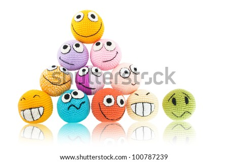 Lot of handmade colored smileys in pyramid and one of them with sad face near it. Isolated on white background. - stock photo