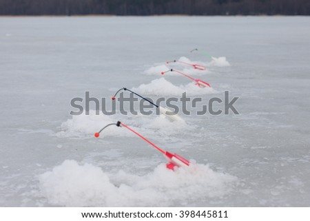 lot of ice fishinng rods on the pond - stock photo