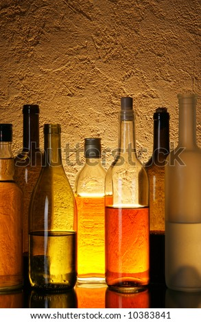 Lots bottles of alcohol drinks over textured background - stock photo
