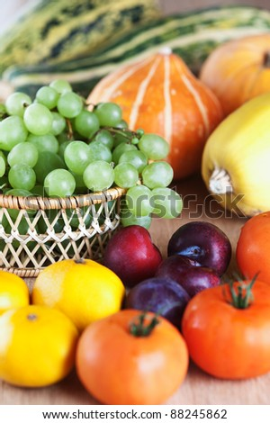 lots fruits vegetables squash bunch grapes basket mandarin plum tomatoes closeup wooden table - stock photo