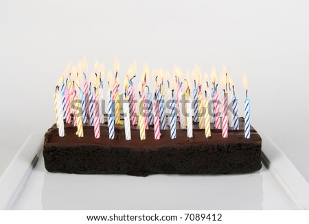 Lots of Birthday Candles lit on a Chocolate Cake - stock photo