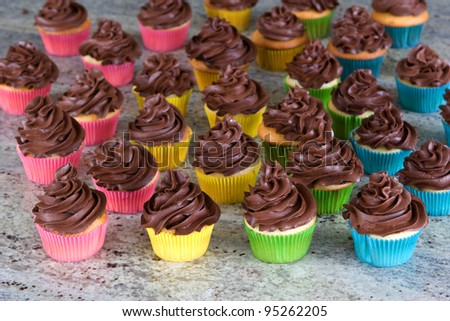 lots of chocolate frosted cupcakes in rainbow wrappers - stock photo
