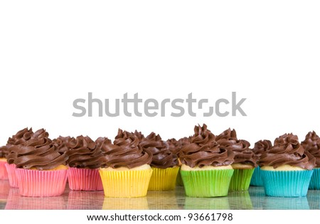 lots of chocolate frosted cupcakes in rainbow wrappers - isolated on white - stock photo
