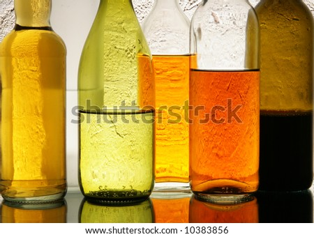 Lots of colorful bottles with alcohol close-up over textured background - stock photo