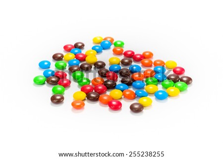 Lots of colorful candies spread on white background - stock photo
