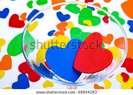 lots of colorful hearts of plastic in a martini glass on a background of hearts are not in focus