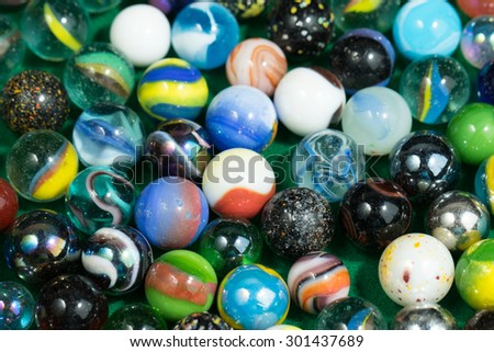 Lots of Colorful Marble Balls on Green background - stock photo