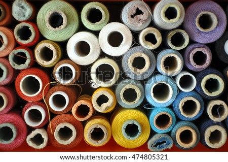 Lots of colorful spools of thread for sewing. Top view, background.