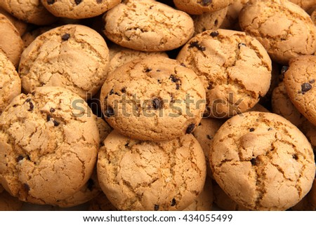 Lots of cookies and biscuits background. Sweet chocolate chips biscuits and cookies texture background. Oatmeal, chocolated drops and other sweets. Dessert, sweets for tea. Fattening sweets concept - stock photo
