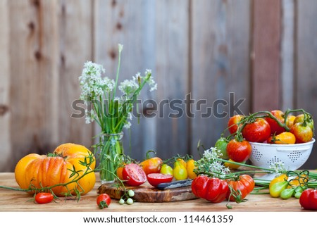 Lots of fresh tomatoes and garlic flowers with wooden background - stock photo