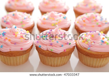 Lots of freshly baked pink cupcakes in rows. - stock photo