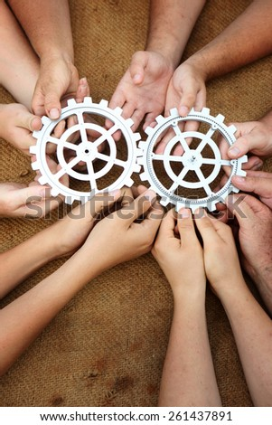 Lots of hands working together - team holding gears - stock photo