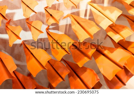 Lots of Paper Aeroplances pushing against wall - stock photo