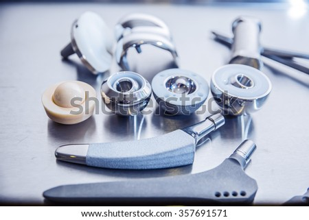lots of parts for transplantation of leg joints and tools for surgical operations on replacement of joints lie against a metal surface - stock photo