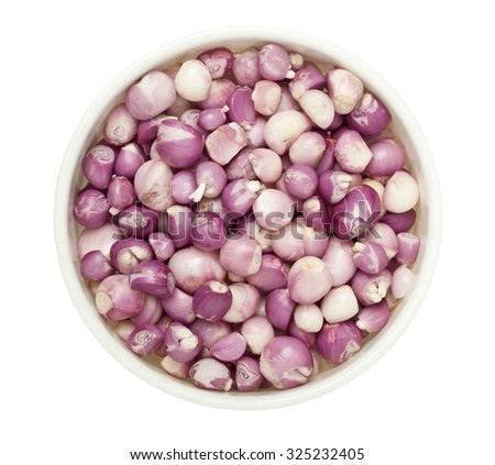 Lots of peeled shallots in a round tray isolated on white background