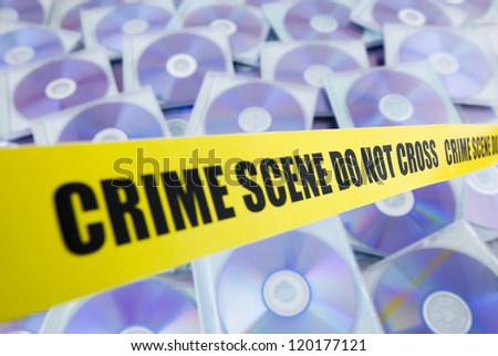 Lots of pirated compact disks enclosed by police tape - stock photo