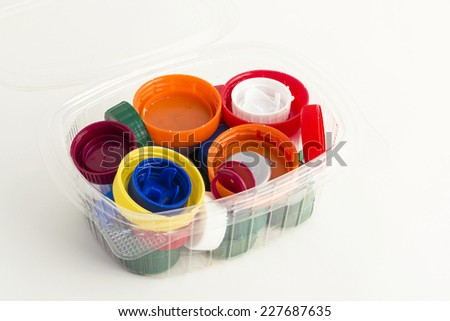 lots of plastic caps in a plastic container isolated on white background  - stock photo