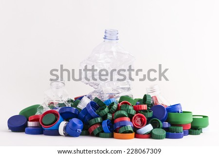 lots of plastic plugs with three crushed plastic bottles isolated on white background  - stock photo