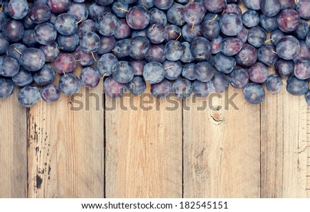 Lots of Plums on Wooden Table - stock photo