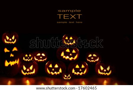 Lots of pumpkins lit brightly against a black background