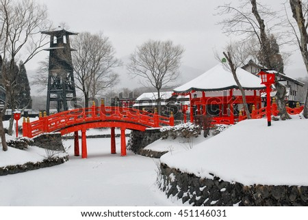 Lots of snow covered on the floor and old Japanese style building and red bridge, Winner in Japan, Hokkaido - stock photo