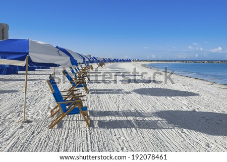 lots of sun loungers and beach umbrellas on silver sand,  vacation concept - stock photo