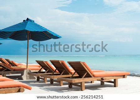 Lots of sunbeds with umbrellas at the ocean beach - stock photo
