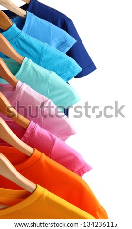 Lots of T-shirts on hangers isolated on white - stock photo