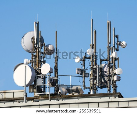 Lots of telcommunication antennas on the roof of a house - stock photo