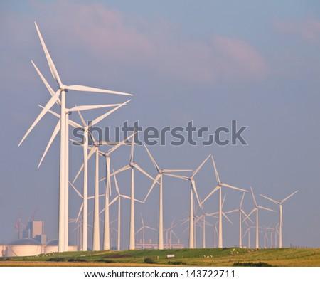 Lots of Three Megawatt Wind Turbines in a Wind farm on the Horizon - stock photo