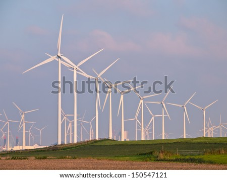 Lots of Three Megawatt Wind Turbines in a Wind farm on the Horizon - stock photo