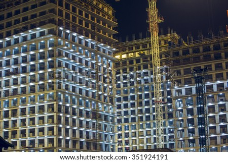 Lots of tower cranes build large residential buildings at night. buildings under construction with cranes and illumination at dark night. night shot of construction equipment at building site.   - stock photo