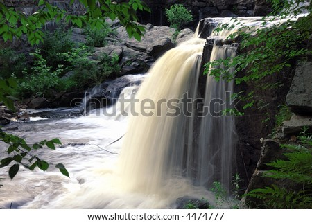 Lots of water gushing through a spring waterfall - stock photo